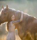 Pferdefotografie bei München: Mädchen mit Tattoos im Kleid mit Pferd im Morgenlicht