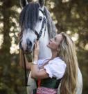 Pferdefotografie bei München: Frau im Dirndl mit PRE-Hengst